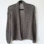 Touch of Merino Cardigan which is a simple crochet cardigan hanging on the wall