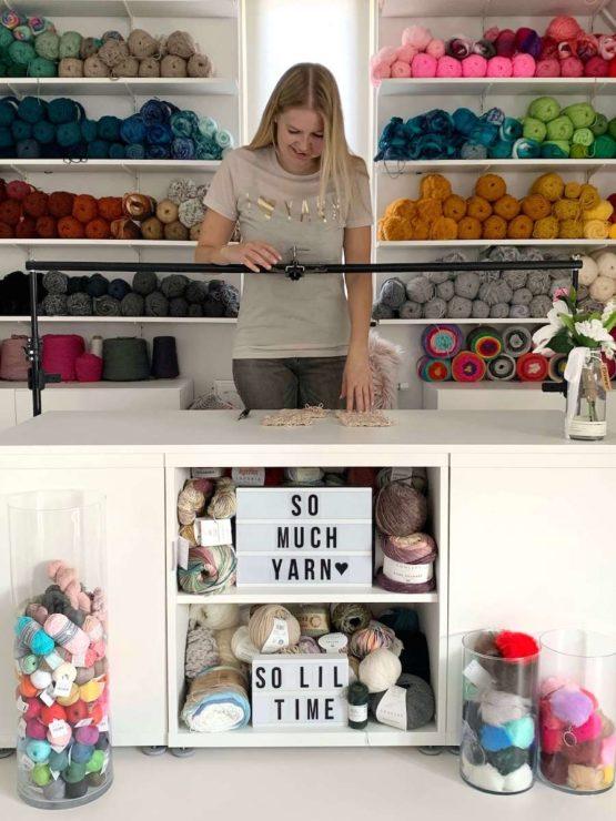 Wilma Westenberg from wilmade.com working in her yarn room studio with huge yarn wall recording youtube video tutorials